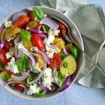 Kartoffelsalat med tomater og mozzarella og rødløg i en skål.