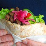 Hjemmelavet kebab i pitabrød med salat, tomater, og syltede rødløg